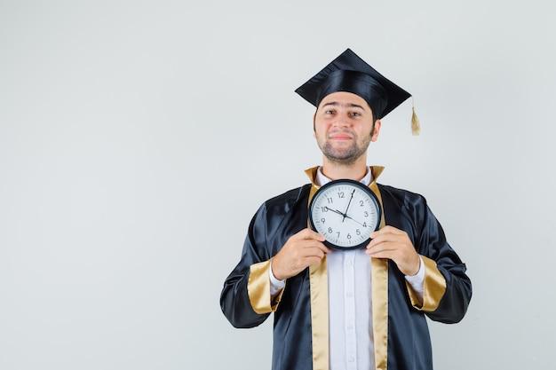 Giovane che tiene l'orologio da parete in uniforme laureato e che sembra allegro. vista frontale.