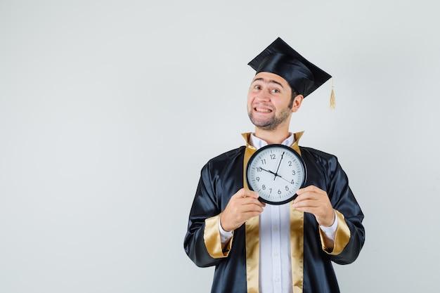 卒業式の制服を着て壁時計を保持し、陽気な、正面図を探している若い男。
