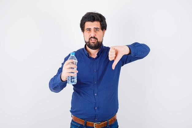 水のボトルを持って、青いシャツとジーンズで親指を下に見せて、真剣に見える若い男。正面図。