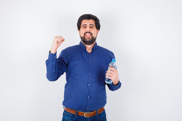 Giovane che tiene in mano una bottiglia d'acqua e mostra un gesto di potere in camicia blu e jeans e sembra ottimista, vista frontale.