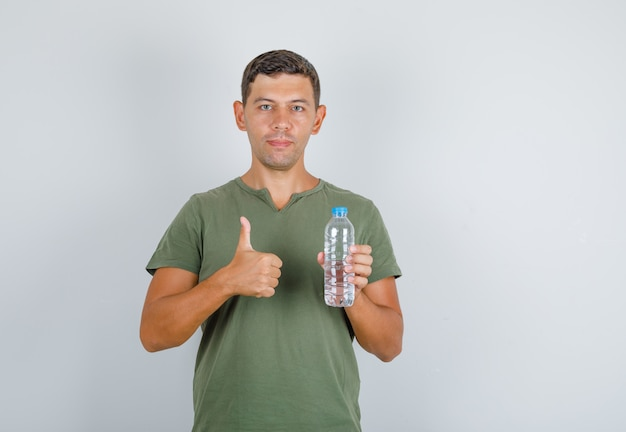 Young man holding water bottle and showing thumb up in army green t-shirt front view.