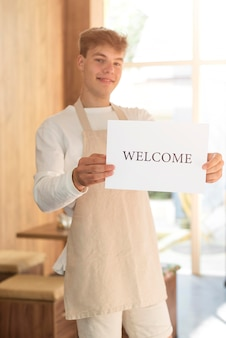 Young man holding a welcome sign after the end of quarantine