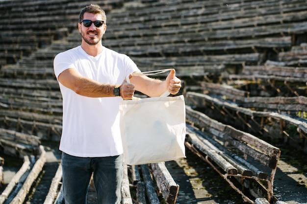 Молодой человек, держащий белую текстильную экологическую сумку на фоне городского города. . концепция защиты экологии или окружающей среды. белая эко-сумка для макета.