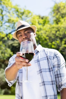 Young man holding wine glass in the garden