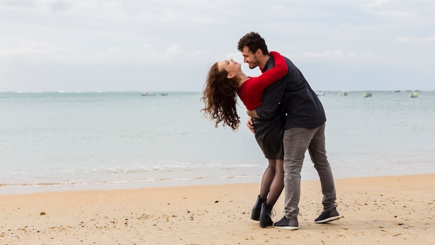 Young man holding woman in arms on sea shore
