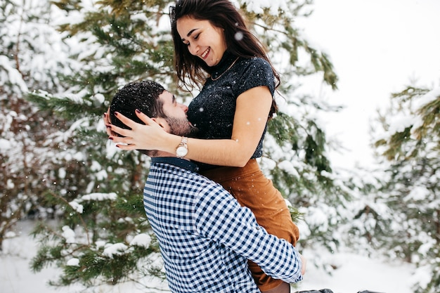 Young man holding woman in arms in winter forest