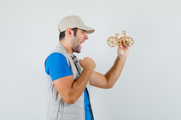 Молодой человек держит деревянный велосипед в футболке, куртке и выглядит счастливым. .