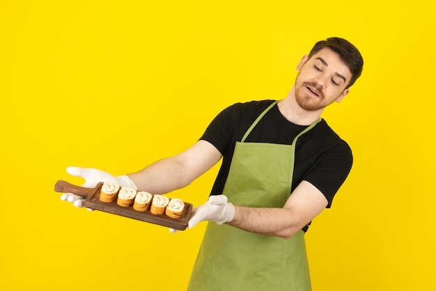 ケーキのスライスでいっぱいの木製トレイを保持している若い男。
