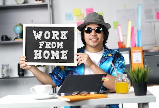 黒板に自宅から仕事を保持している若い男