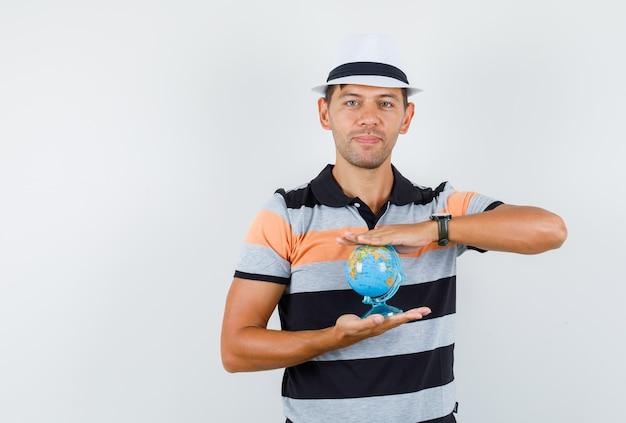 Giovane che tiene il globo del mondo in maglietta e cappello e che osserva attento