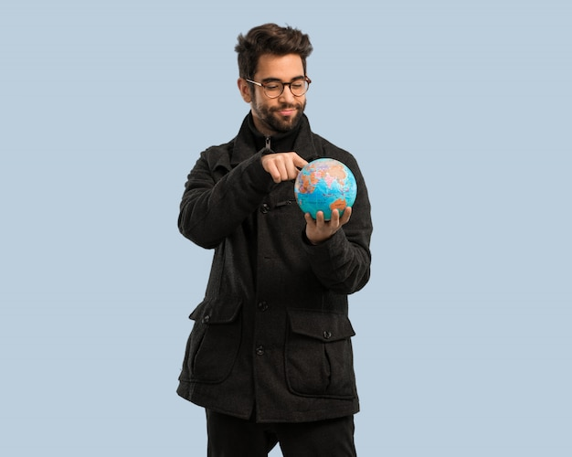 Young man holding a world globe