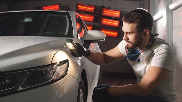 Молодой человек держит в руке фонарик и проверяет качество нанокерамического покрытия на кузове автомобиля