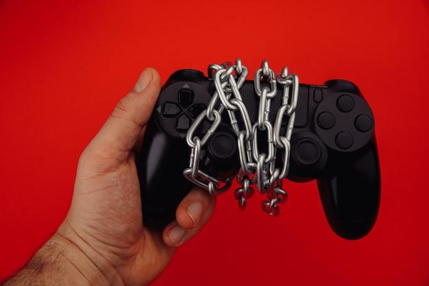 若い男がゲーム コントローラーを保持しています。