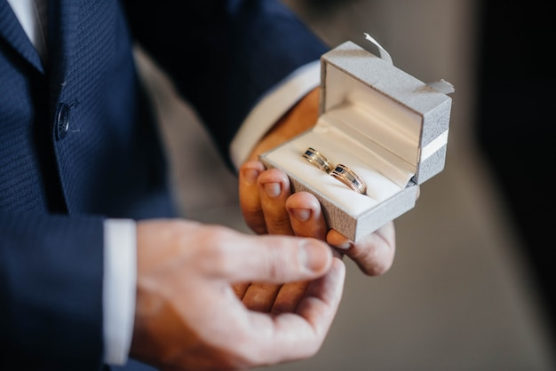 A young man holds a box with wedding rings close-up.