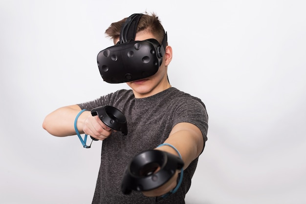 A young man holds controllers for a viar game. a teenager plays with virtual reality glasses and considers joysticks and gamepads