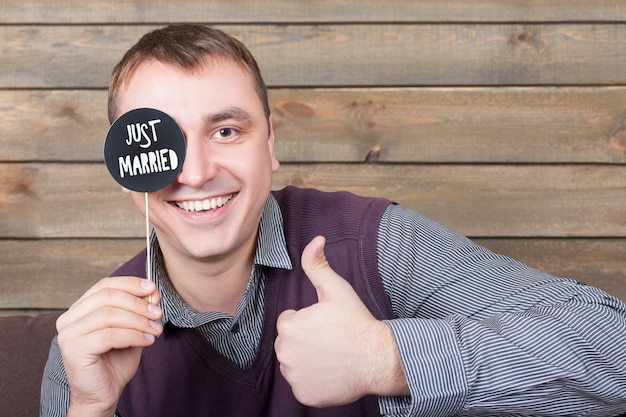Young man holds funny icon on a stick with just married inscription and show thumbs up sign