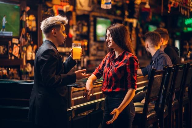 若い男が手にビールのグラスを保持し、スポーツパブ、フットボールのファンの幸せなレジャーでバーのカウンターで女性と会談