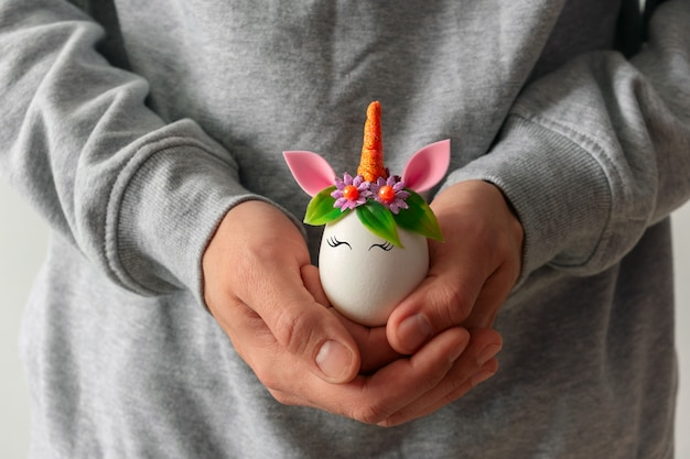 Young man holds in hands easter egg decorated as a cute unicorn