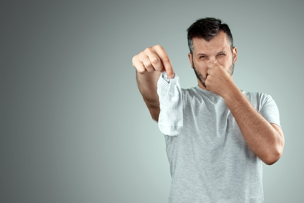 A young man holds his smelly socks and covers his nose with his hand
