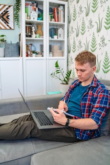 A young man holds a laptop on his lap while sitting on the couch and work remotely from home