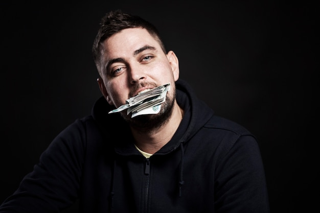 A young man holds money in his mouth. black background. close-up.