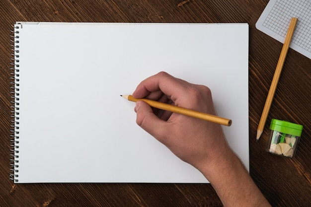 A young man holds a pencil in his hand over a sketchbook with white sheets
