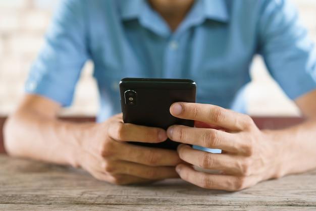 젊은 남자가 그의 손에 전화를 보유하고 온라인 게임을하는 테이블에 앉아 문자 메시지를 보냅니다.