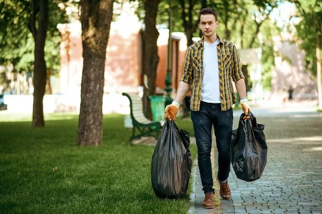 Молодой человек держит пластиковые мешки для мусора в парке, волонтерство