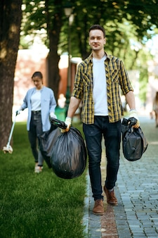 Young man holds plastic trash bags in park, volunteering. male person cleans forest, ecological restoration, eco lifestyle, garbage collection and recycling, ecology care, environment cleaning