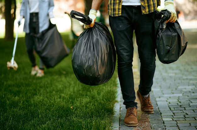 Young man holds plastic trash bags in park, volunteering. male person cleans forest, ecological restoration, eco lifestyle, garbage collection and recycling, ecology care