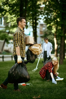 Young man holds plastic trash bags in park, volunteering. male person cleans forest, ecological restoration, eco lifestyle, garbage collection and recycling