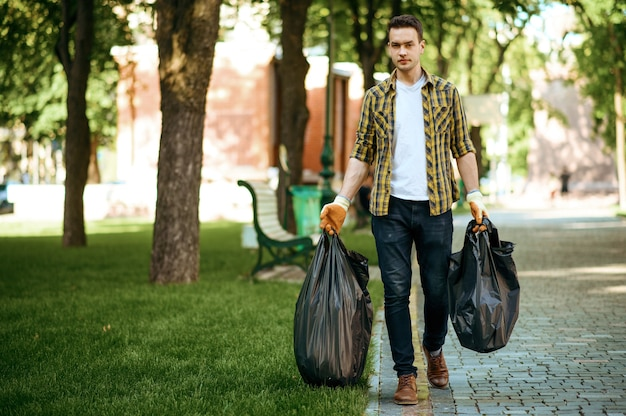 Young man holds plastic trash bags in park, volunteering