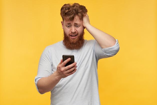 若い男は、スマートフォンを持って、ディスプレイに主演する困惑した、混乱した表情で彼の頭に触れます