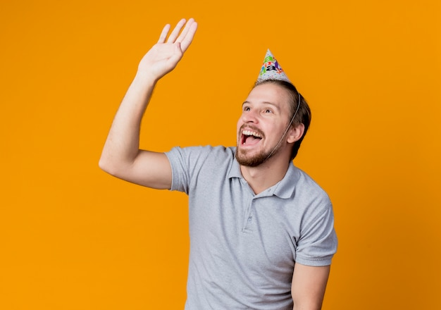 Young man in holiday cap looking aside waving with hand smiling cheerfully birthday party concept standing over orange wall