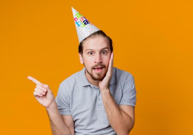 Giovane uomo in vacanza cap sorpreso pointign con il dito sul lato festa di compleanno concetto in piedi sopra la parete arancione