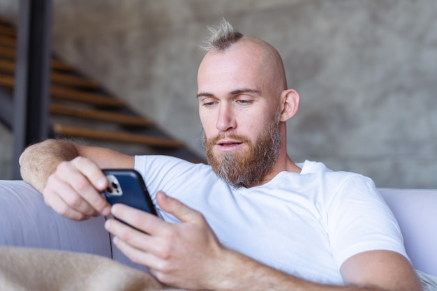 A young man at home on the couch comes off with a cozy warm blanket, holds a mobile phone, reads the news, watches a video