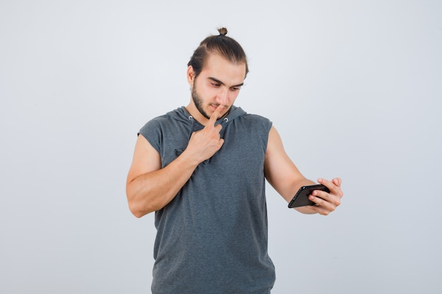 Young man in hooded t-shirt holding fingers on mouth, looking at phone and looking wistful , front view.