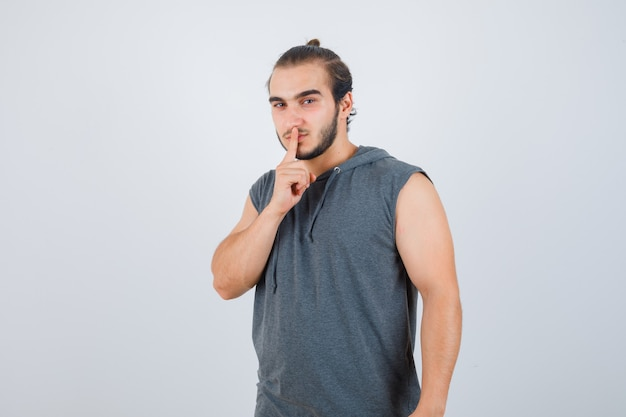 Young man in hooded t-shirt showing silence gesture and looking serious , front view.