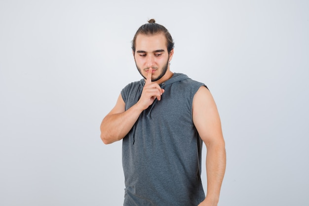 Young man in hooded t-shirt showing silence gesture and looking upset , front view.