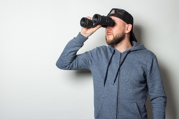 Young man in a hoodie and a cap looks through binoculars against a light wall