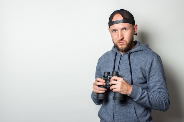 Young man in hoodie and cap with serious face holding binoculars