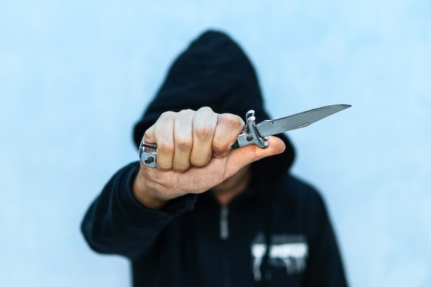 A young man in a hoodie holding a knife symbolizing youth crime. crime concept. the threat of a cold weapon. a terrorist from isis with a knife. a prisoner with a shiv.