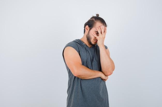 Giovane uomo in felpa con cappuccio pendente faccia a portata di mano e guardando stanco, vista frontale.
