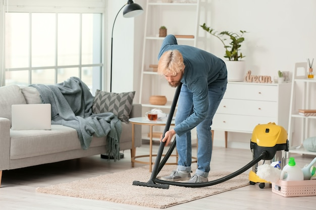 Young man hoovering carpet at home