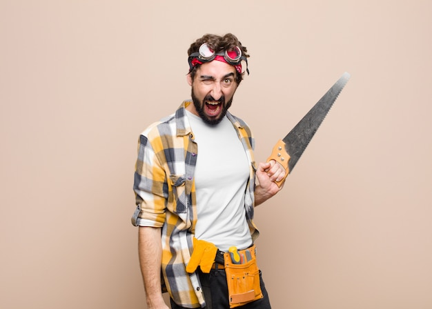 Young man housekeeper holding a saw on flat wall