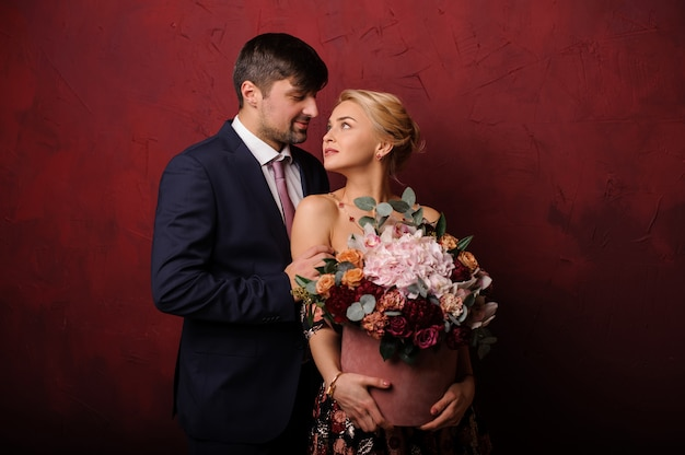 Young man hug his woman with the bouquet of flowers and looking in her eyes