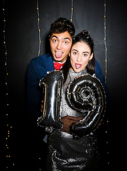 Young man hugging attractive woman with balloons numbers and showing tongues