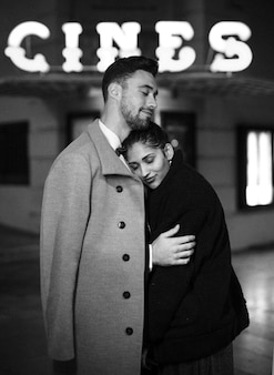 Young man hugging charming attractive woman on street