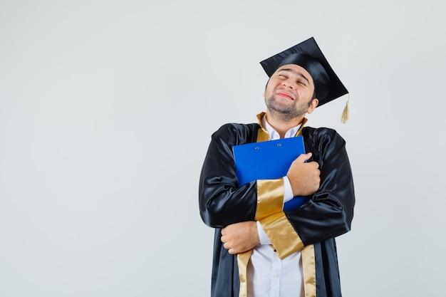 대학원 유니폼 클립 보드를 포옹 하 고 평화로운 찾고 젊은 남자. 전면보기.