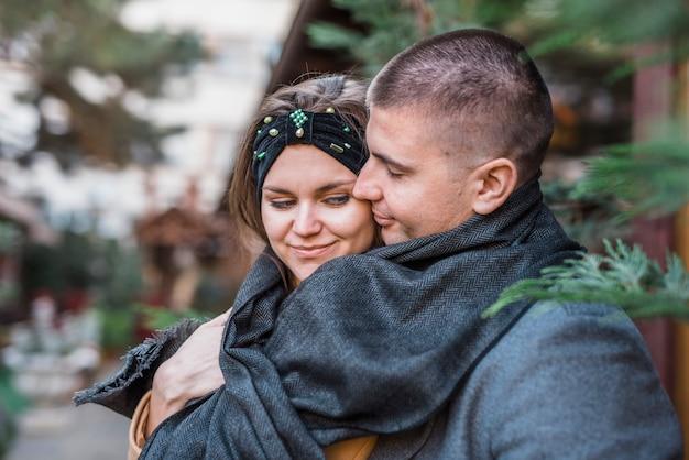Giovane che abbraccia da donna sorridente affascinante posteriore in sciarpa
